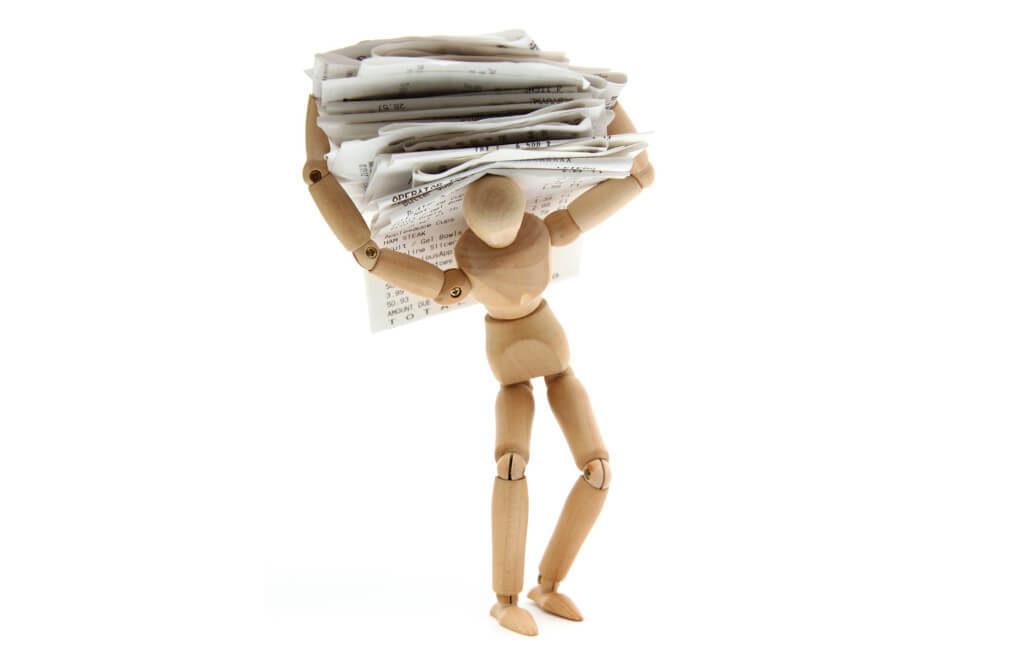деревянная фигурка человека под грузом бумаг